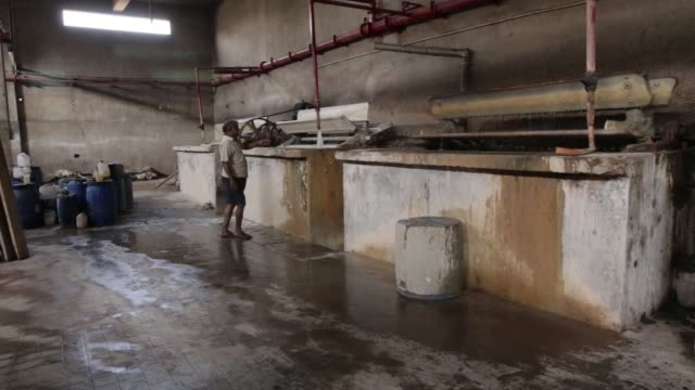 Spinning paddles operate over a vat during a dehairing process at the Sheong Shi Tannery in Kolkata West Bengal India on Tuesday Dec 26 Close up...