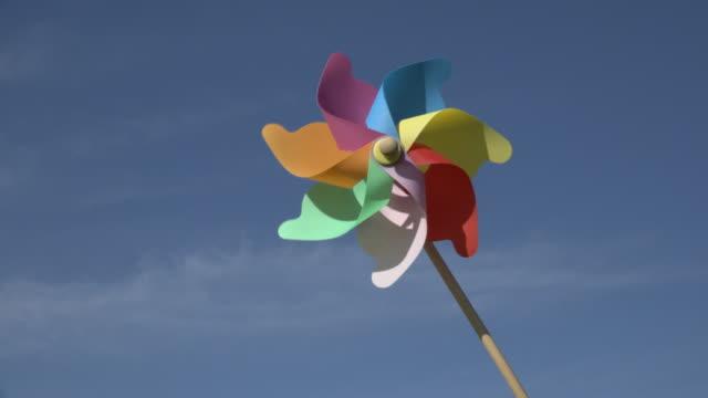 spinning pinwheel at blue sky - girandola video stock e b–roll