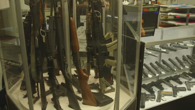 stockvideo's en b-roll-footage met spinning rack of rifles in gun shop, medium shot - vuurwapenwinkel