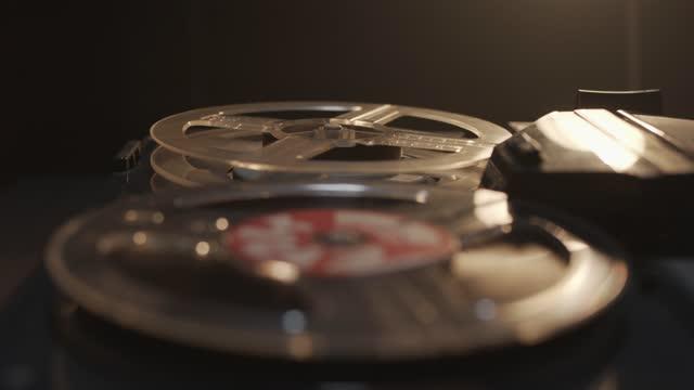 音楽と音声レコードで古い、傷ついたほこりっぽいテープレコーダーの回転リール。クローズアップ - 盗み聞き点の映像素材/bロール