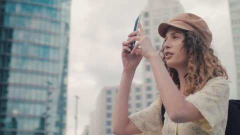 vídeos y material grabado en eventos de stock de spinning shot of young woman in central berlin taking photo with phone - guay