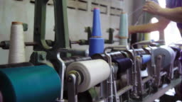 Spinning Spools Wheel of Colourful Threads on a Loom Machine.