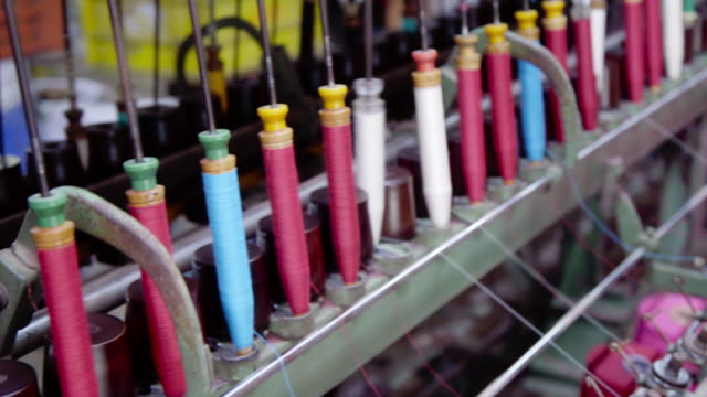 vidéos et rushes de spinning spools wheel of colourful threads on a loom machine. - usine textile