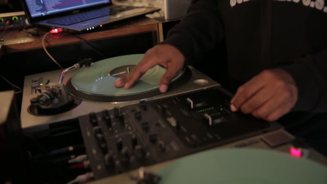 dj spinning vinyl in record store, medium shot - obscured face stock videos & royalty-free footage