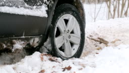 Spinning wheel of a car stuck in snow.