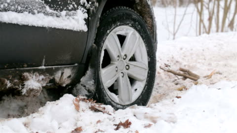 spinning wheel of a car stuck in snow. - sliding stock videos & royalty-free footage