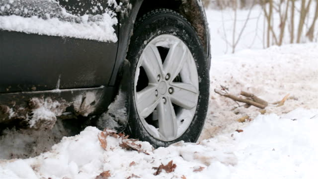 spinning wheel of a car stuck in snow. - tyre stock videos & royalty-free footage