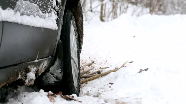 spinning wheel of a car stuck in snow. - trapped stock videos & royalty-free footage
