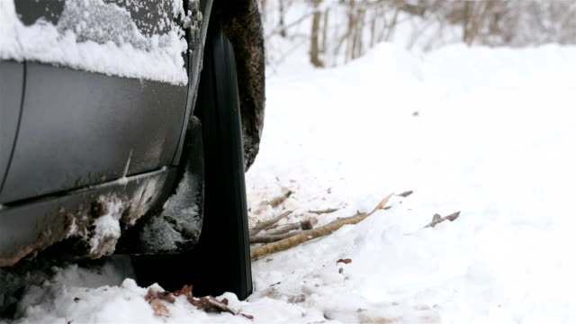 車の回転車輪は雪の中で立ち往生しています。 - 横滑り点の映像素材/bロール