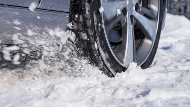ruota rotante di un'auto bloccata nella neve - traccia video stock e b–roll
