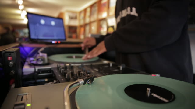 dj spins vinyl records on turntables in record store, medium shot - obscured face stock videos & royalty-free footage