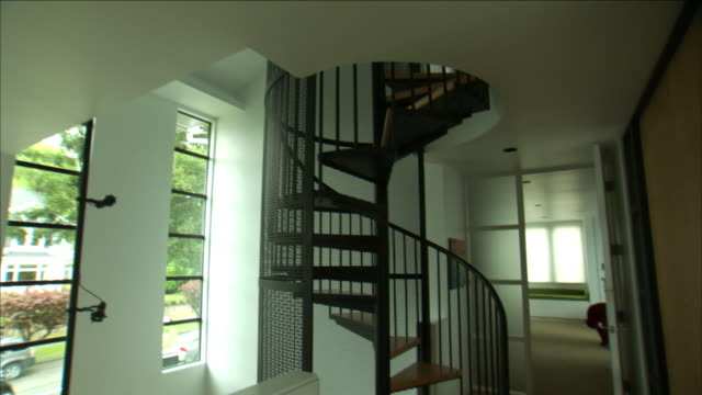 a spiral staircase leads to the second floor of a house next to a contemporary bedroom. - spiral staircase stock videos & royalty-free footage