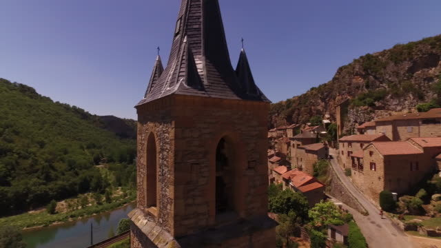 spiralling drone aerial around church spire to view of millau viaduct - viaduct stock videos & royalty-free footage