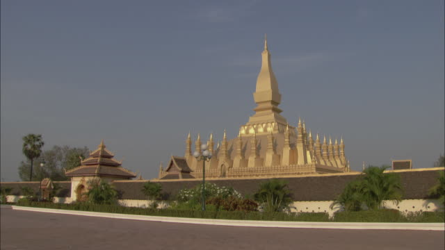 a spire tops pha that luang in laos. - spire stock videos & royalty-free footage