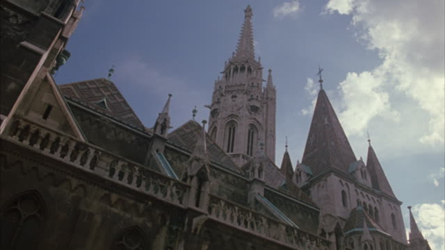 stockvideo's en b-roll-footage met spires of budapest's matthias church reach into a blue sky. - torenspits