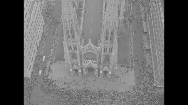 vídeos de stock e filmes b-roll de spires of st patrick's cathedral in new york city / back of atlas statue at rockefeller center / aerials of cathedral and crowded 5th avenue / church... - estátua de atlas