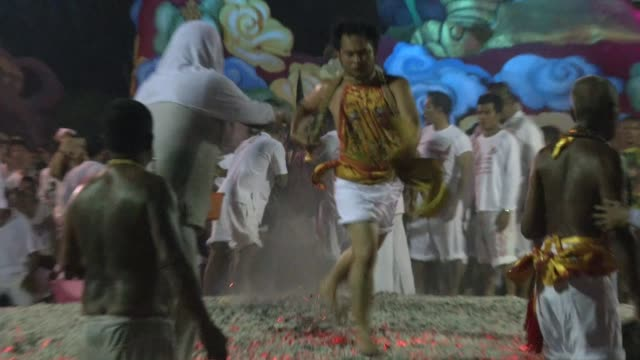 spirit mediums walk on burning coals at the phuket vegetarian festival in phuket town, thailand. the event is held over a nine-day period in october,... - mascolinità video stock e b–roll