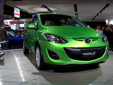 WS Spirited Green Metallic Mazda2 hatchback revolving on turntable WS HA front threequarter passenger side view of green Mazda2 with white...