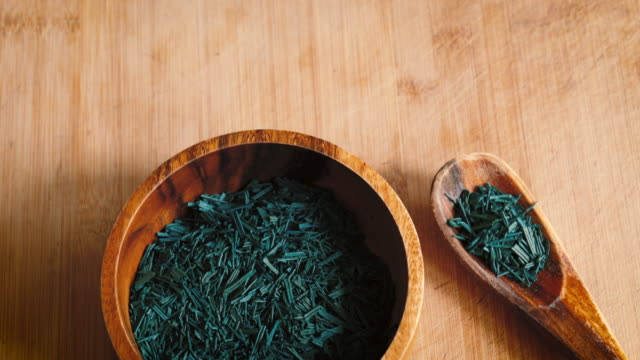 Spirulina Algae Flakes in Wooden Bowl & Spoon Close Up