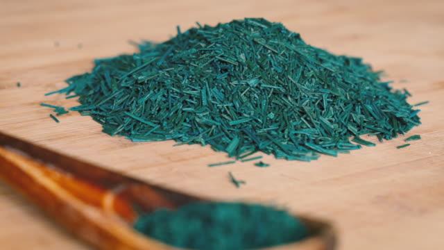 vídeos y material grabado en eventos de stock de copos de algas espirulina en tablero de madera y cuchara - antioxidante
