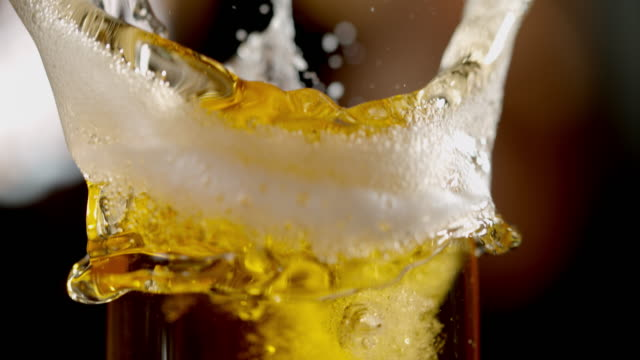 vídeos de stock e filmes b-roll de slo mo splashing beer in a glass - beer alcohol