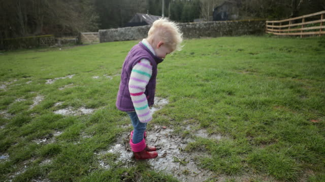 splashing in muddy puddles - wellington boot stock videos & royalty-free footage