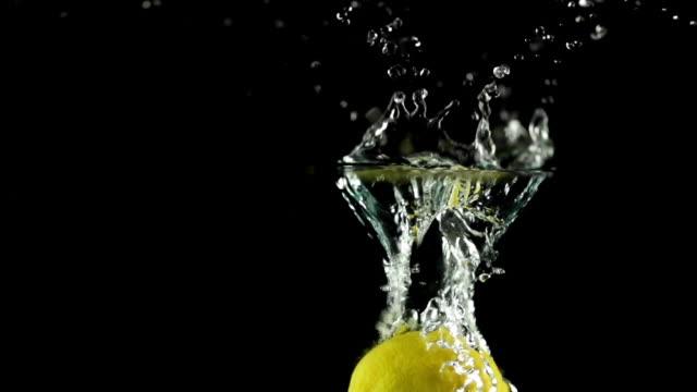 slow motion: splashing lemon - lemon stock videos & royalty-free footage