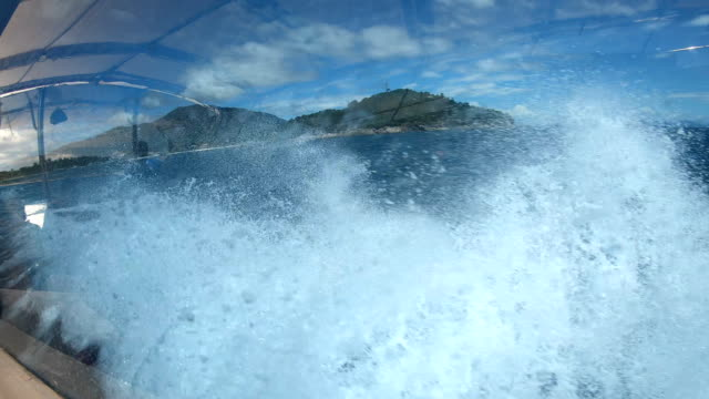 splashing sea waves water hitting boat and adang island with blue sky seen from side view of speedboat moving on ocean - yachting stock videos & royalty-free footage