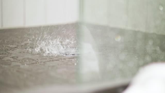 vidéos et rushes de projections d'eau sur carrelage bac à douche - bonde