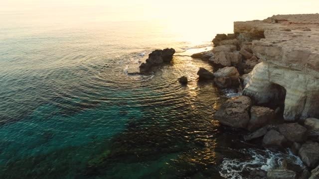 splashing waters of blue lagoon, ayia napa, cyprus. aerial drone shot. - republic of cyprus stock videos and b-roll footage