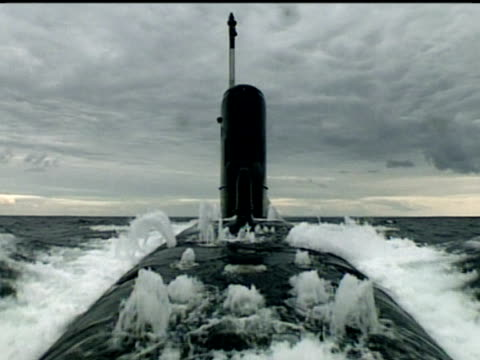 HMS Splendid submerges as bubbling white foam surrounds submarine that descends into dark green water.