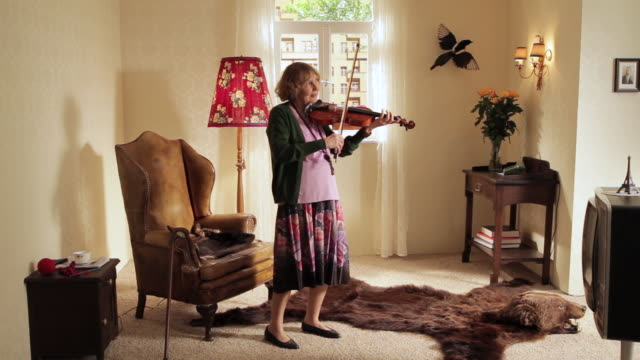 ws pan split screen showing  senior woman playing violin while man playing guitar / berlin, germany - gegensatz stock-videos und b-roll-filmmaterial