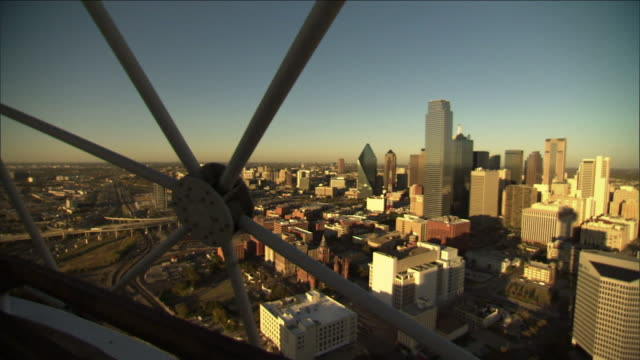 spoked structures frame a view of the city of  dallas, texas. - speichen stock-videos und b-roll-filmmaterial