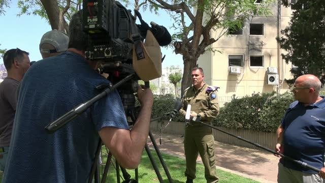 vidéos et rushes de spokesman for the israeli army informs the media in front of a residential building which was hit by a rocket fired from the gaza strip on may 11,... - caméraman