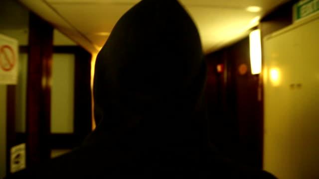 di spaventoso uomo con cappuccio nel corridoio dell'hotel - cappuccio video stock e b–roll