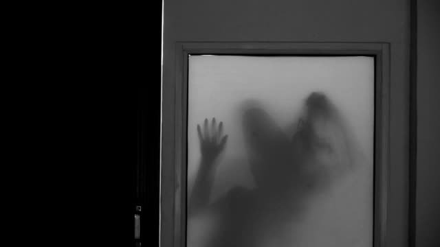 spooky silhouette of ghost woman behind the matte glass window - illusion stock videos & royalty-free footage