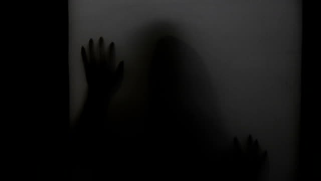 Spooky silhouette of ghost woman behind the matte glass window