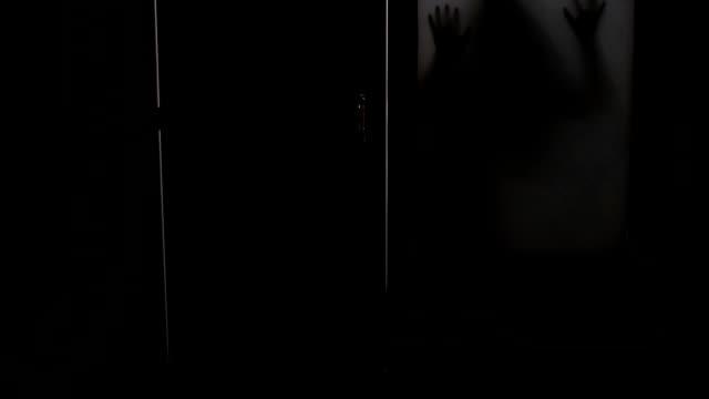 vídeos de stock e filmes b-roll de spooky silhouette of ghost woman behind the matte glass window - retroiluminado