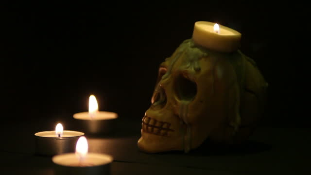 spooky skull on a bier lighted by candles