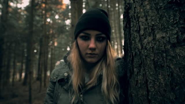 vídeos y material grabado en eventos de stock de pov spooky mujer joven escudan detrás de un árbol - perseguir