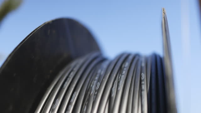 stockvideo's en b-roll-footage met spoel van glasvezelkabel spinnen terwijl ze worden geïnstalleerd op telefoonpalen in een woonwijk - cable