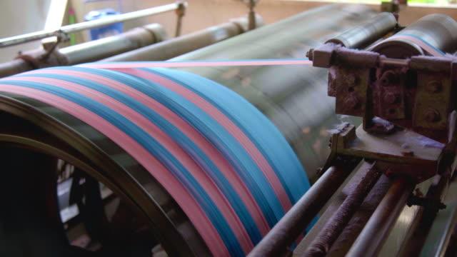 vídeos y material grabado en eventos de stock de husillo de bobina de hilos de colores en telar, industria de telas en la fábrica textil. - bobina