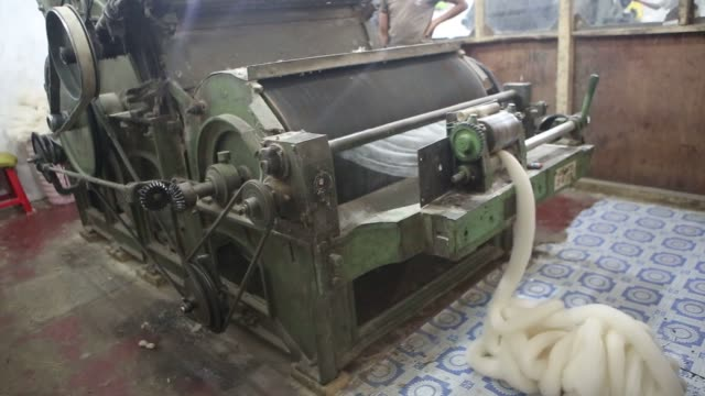 spools of de haired pashmina is processed into threads at the spinning unit of the valley wool ltd factory and a store owner displays shawls in... - man and machine stock videos & royalty-free footage