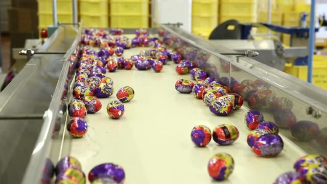 spools of foil used for wrapping cadbury creme eggs move through packaging machinery at the bournville cadbury factory operated by mondelez... - chocolate factory stock videos & royalty-free footage