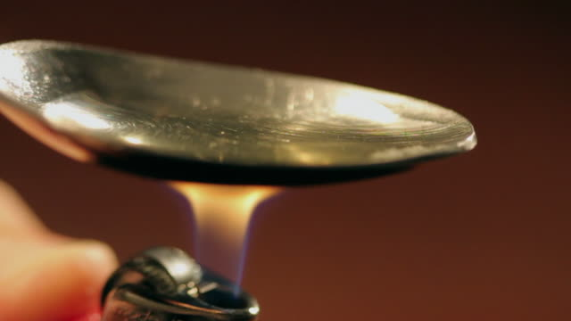 ECU SELECTIVE FOCUS Spoon being heated to dissolve heroin / Los Angeles, California, USA