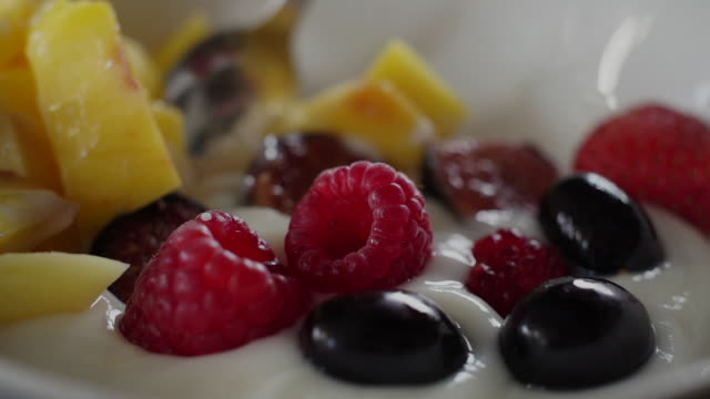 CU SLO MO spoon mixing yogurt and fruit together/ Johannesburg/ South Africa