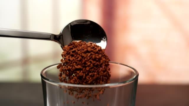 vidéos et rushes de cuillère de café instantané tombant dans la cuvette en verre - tasse