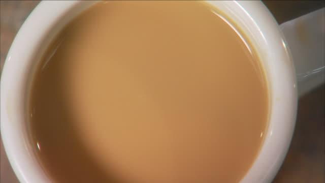 vídeos de stock, filmes e b-roll de a spoon stirs coffee in a cup where a coffee bean floats on top. - xícara