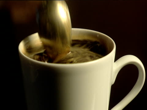 spoon stirs cup of black coffee - spoon stock videos and b-roll footage