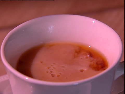 a spoon stirs milk into a cup of tea. - black tea stock videos & royalty-free footage